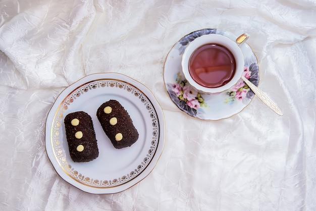 Xícara de chá e um prato de bolos em tecido branco