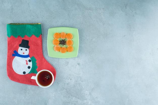 Xícara de chá e uma meia de natal ao lado de marmeladas em torno de anis em uma bandeja de mármore.