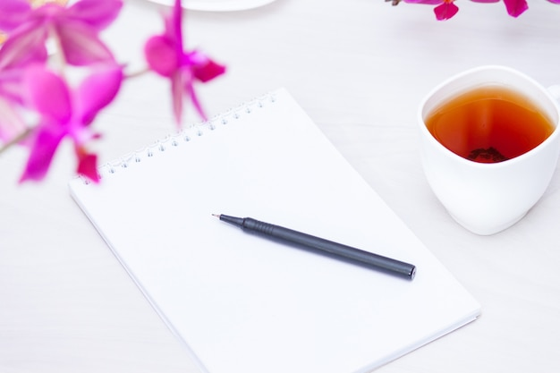 Xícara de chá, flores, caderno de papel. redação, conceito freelance.