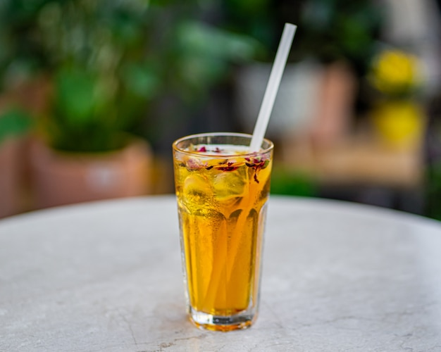 Xícara de chá gelado fresco na mesa com superfície de flores da natureza