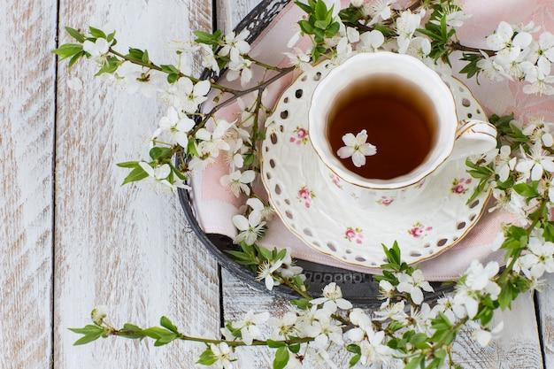 Xícara de chá, guardanapo e ramos de cerejeira em flor