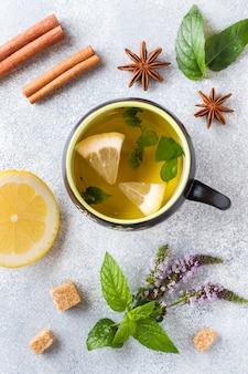 Xícara de chá, hortelã e limão, canela de açúcar mascavo e anis em uma mesa cinza