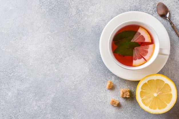 Xícara de chá, hortelã e limão na mesa cinza com fundo copyspace.