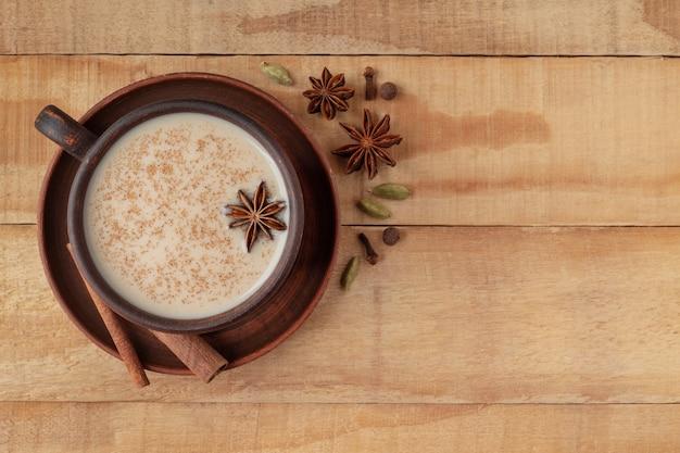 Xícara de chá indiano masala chai com condimentos em fundo de madeira
