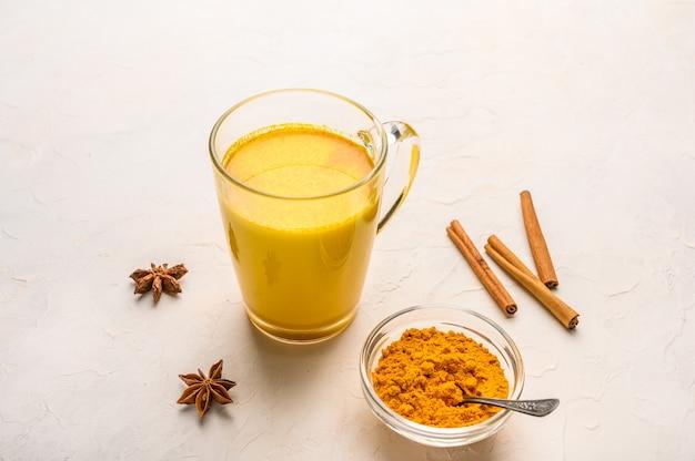 Xícara de chá indiano tradicional masala chai com ingredientes acima sobre superfície de textura branca