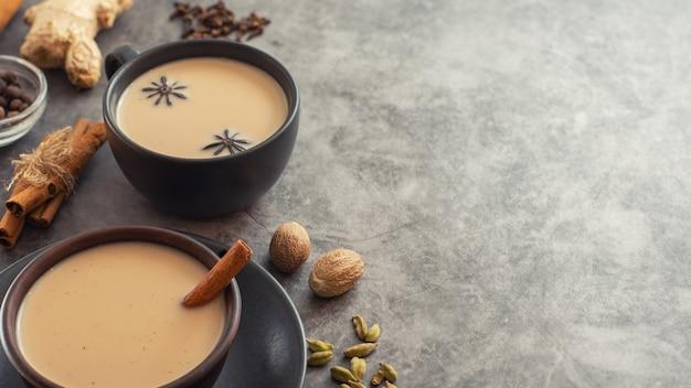 Xícara de chá indiano tradicional masala chai com ingredientes: canela, cardamomo, anis, noz-moscada. com espaço de cópia