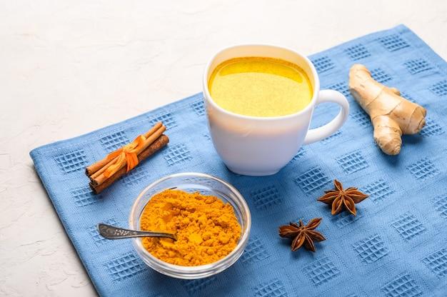 Xícara de chá indiano tradicional masala chai em guardanapo azul com ingredientes acima, sobre superfície de textura branca com espaço