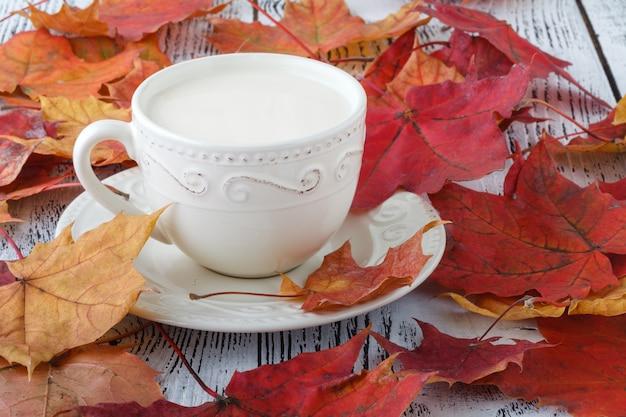 Xícara de chá inglês com leite na mesa branca com folhas de plátano