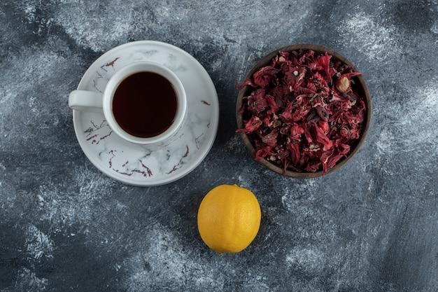 Xícara de chá, limão e tigela de flores secas na mesa de mármore.