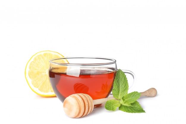 Xícara de chá, limão, hortelã e dipper isolado no branco