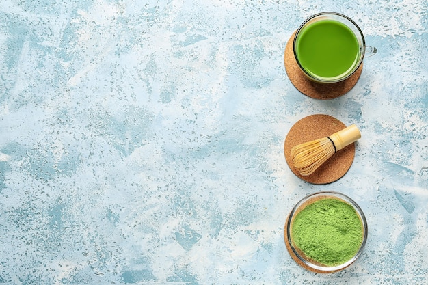 Xícara de chá matcha, pó e chasen na cor de fundo