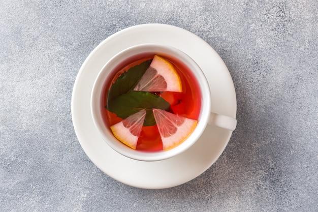 Xícara de chá, menta e limão na mesa cinza com espaço de cópia