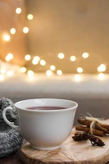 Xícara de chá na almofada quente com luzes