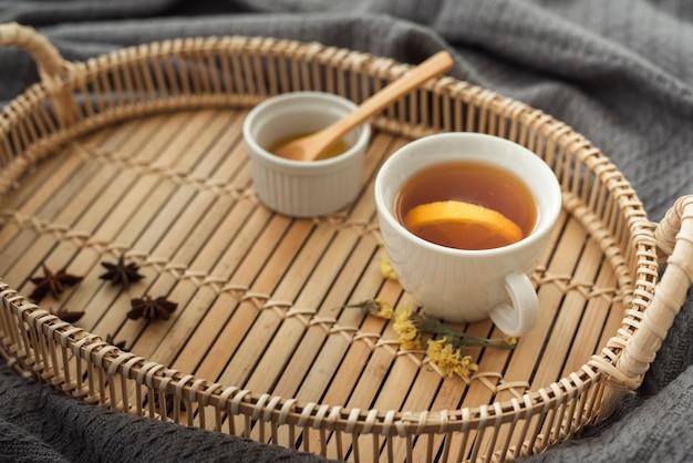 Xícara de chá na bandeja de madeira com mel