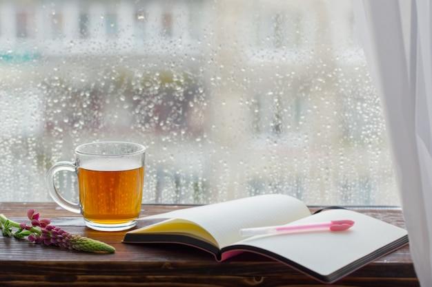 Xícara de chá na janela com gotas de chuva ao pôr do sol