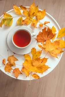 Xícara de chá na mesa de centro de madeira com folhas amarelas do outono. conceito de conforto e relaxamento