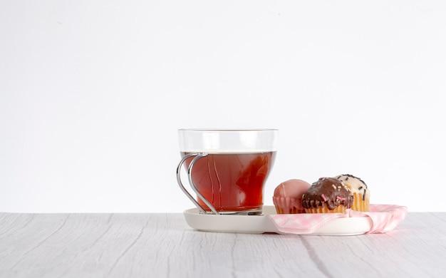 Xícara de chá na mesa de madeira acompanhada de mini cupcakes de diferentes cores e sabores