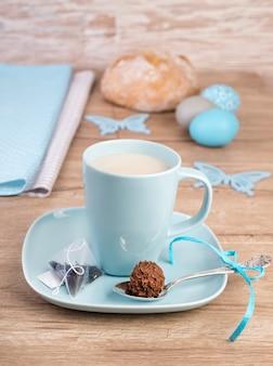Xícara de chá na mesa de madeira com decorações de páscoa