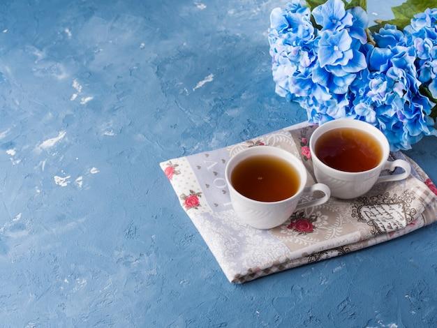 Xícara de chá no fundo azul com flores e têxteis