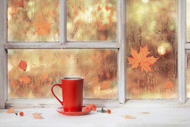 Xícara de chá no parapeito da janela de madeira branca no outono