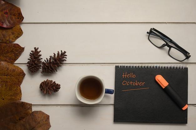 Xícara de chá nota com palavras olá outubro e óculos em um fundo de madeira conceito de outono