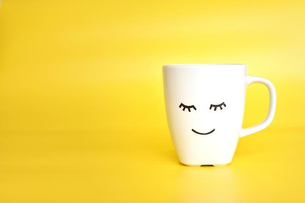 Xícara de chá ou café branco com rosto bonito de olhos fechados, bom dia