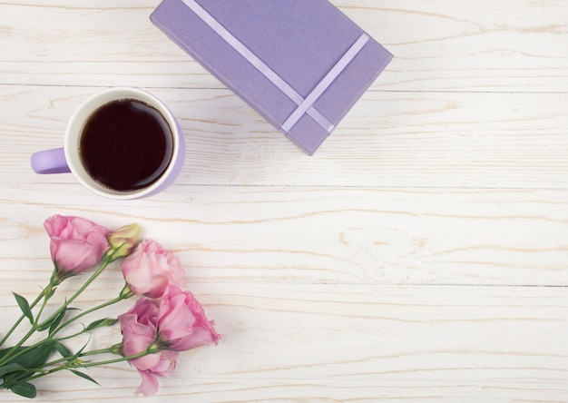 Xícara de chá ou café, caixa de presente e flores cor de rosa