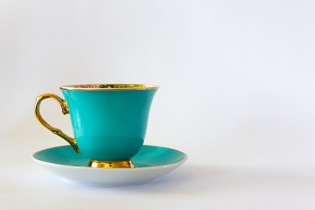 Xícara de chá ou café ciano com guarnição do ouro sobre fundo branco. foco seletivo. copie o espaço.