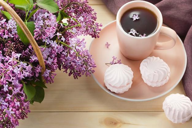 Xícara de chá ou café com marshmallows rosa doces e buquê de lilás em uma cesta. café da manhã.