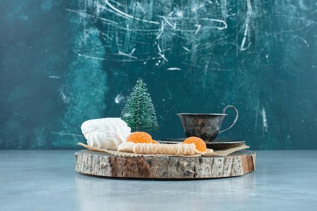 Xícara de chá, pacote de sobremesas e uma estatueta de árvore em uma placa de madeira no mármore.