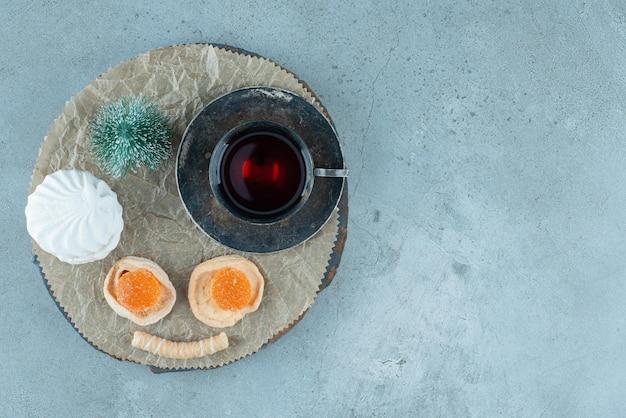 Xícara de chá perfumada, pacote de sobremesas e uma estatueta de árvore em uma placa de madeira no mármore.