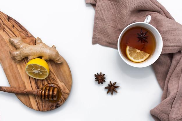 Xícara de chá perto de placa de madeira com mel e limão
