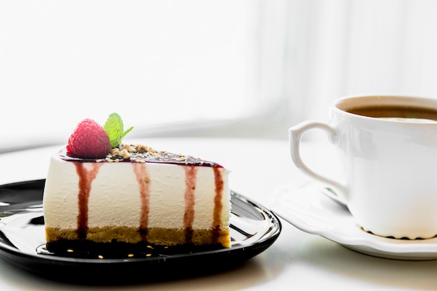 Xícara de chá perto do cheesecake caseiro com frutas frescas e hortelã para a sobremesa na mesa