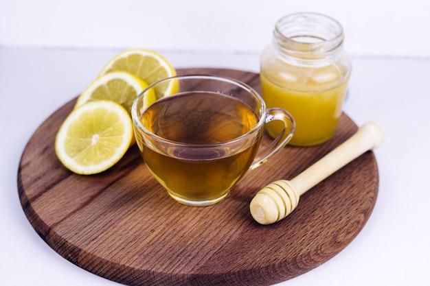 Xícara de chá, pote de mel e limão