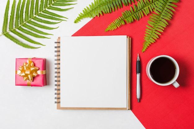 Xícara de chá preto; caneta; bloco de notas e caixa de presente, dispostas em uma linha sobre a superfície vermelha e branca