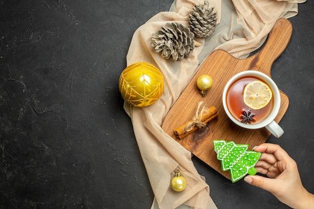 Xícara de chá preto com acessórios de decoração de limão e lima com canela na tábua de madeira