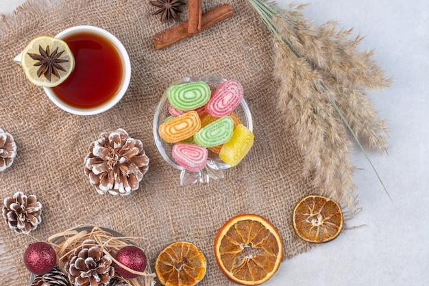 Xícara de chá preto com doces coloridos na superfície de pedra.