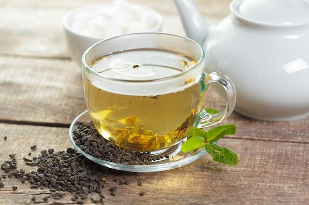 Xícara de chá preto com folhas de hortelã em uma madeira