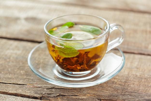 Xícara de chá preto com folhas de hortelã em uma mesa de madeira