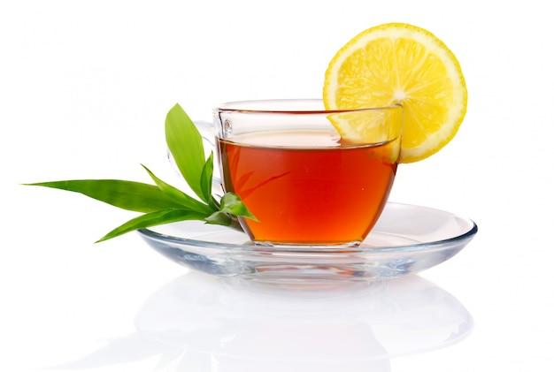 Xícara de chá preto com limão e folhas verdes isoladas