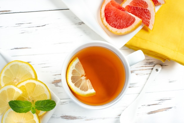Xícara de chá preto com limão e toranja, close-up no fundo branco de madeira