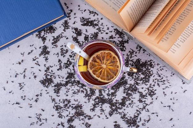 Xícara de chá preto com livros e fatias de frutas. foto de alta qualidade