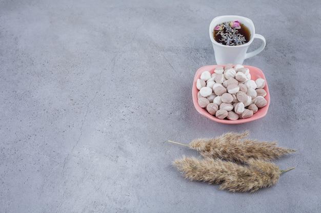 Xícara de chá preto com tigela de doces marrons em fundo de pedra.
