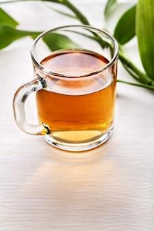 Xícara de chá preto e folhas verdes