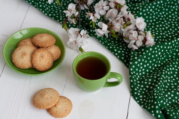 Xícara de chá preto em um guardanapo verde, biscoitos caseiros, um ramo de flor de damasco