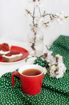 Xícara de chá preto em um guardanapo verde, biscoitos caseiros, uma planta decorativa em uma panela