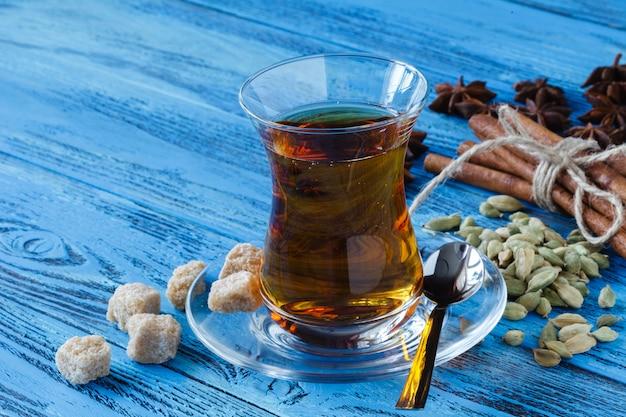 Xícara de chá preto na mesa de madeira com cubos de açúcar de cana