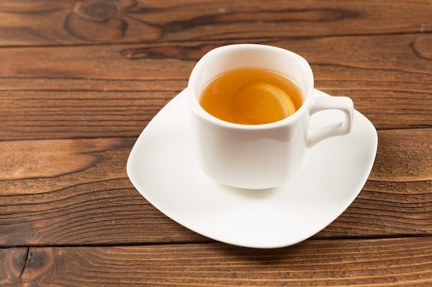 Xícara de chá preto na mesa de madeira