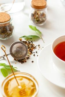 Xícara de chá preto quente na mesa branca com bule de chá seco