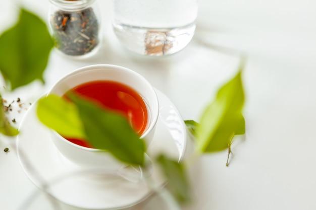 Xícara de chá preto quente na mesa branca com jarra de chá seco